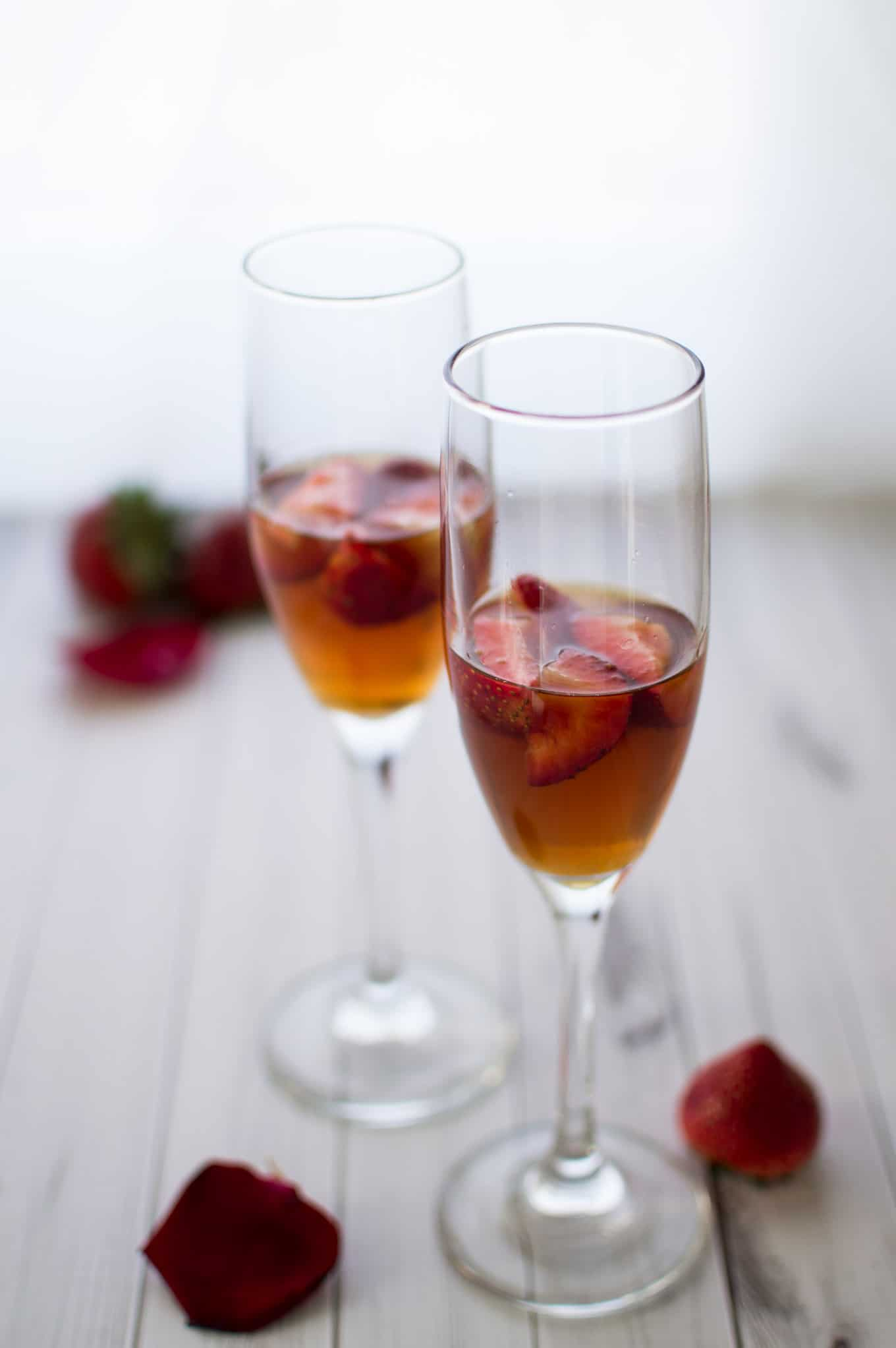 Close up of champagne glasses half-filled with strawberries and fig vodka.