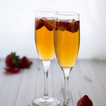 Two champagne glasses filled with cocktails and fresh strawberries.
