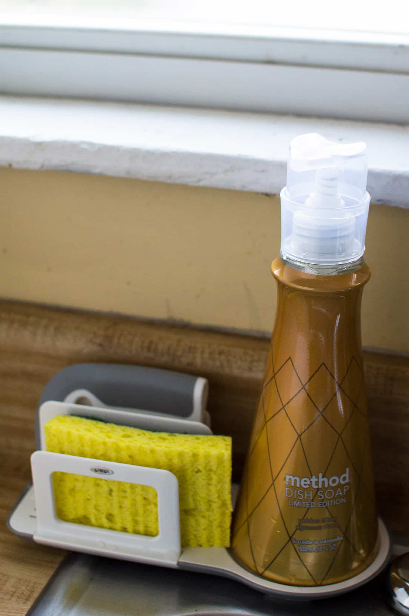 A bottle of dish soap, sponge, and dish squeegee on a sink organizer.