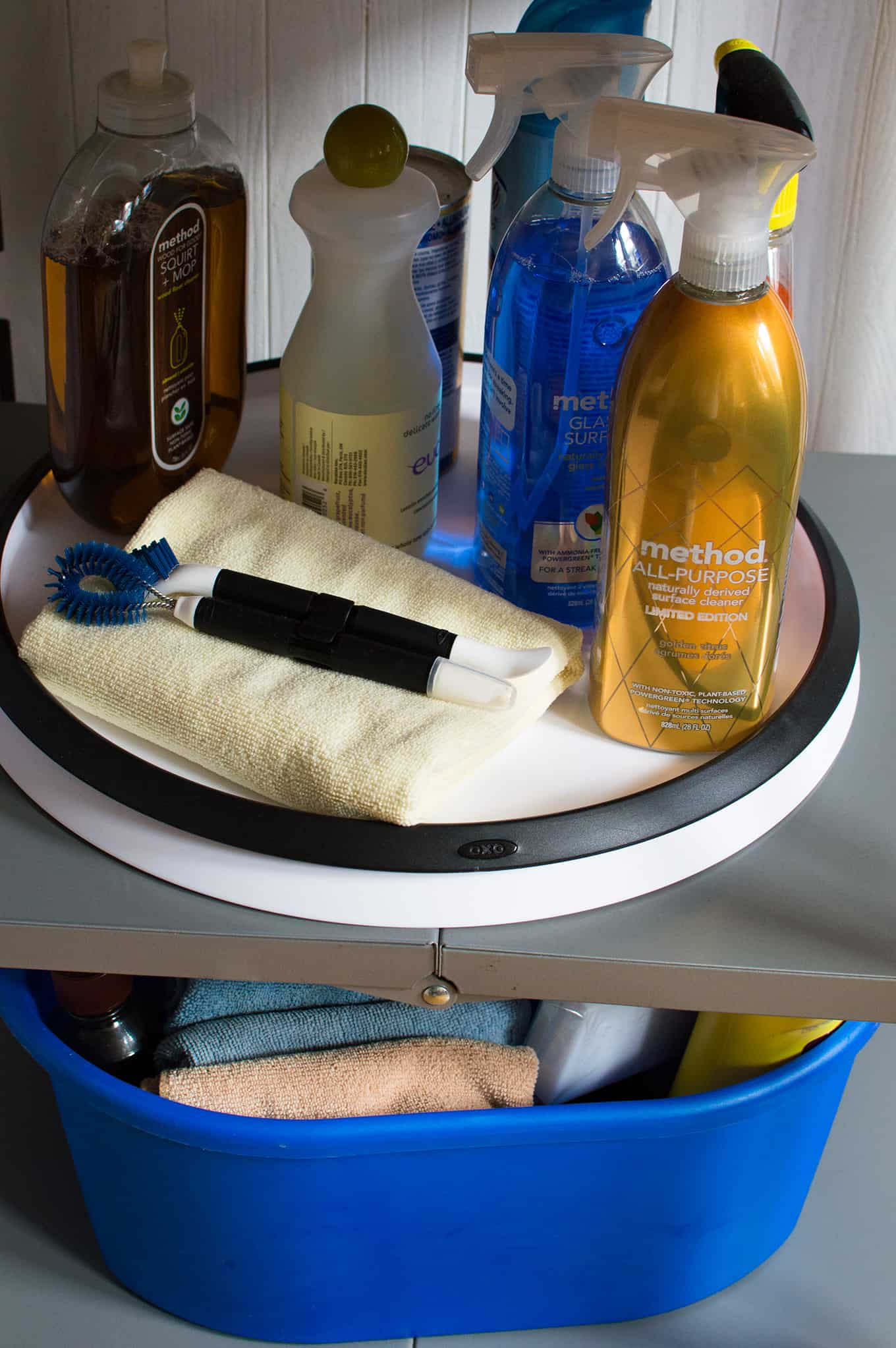 Assorted cleaning supplies and towel on a rotating tray.