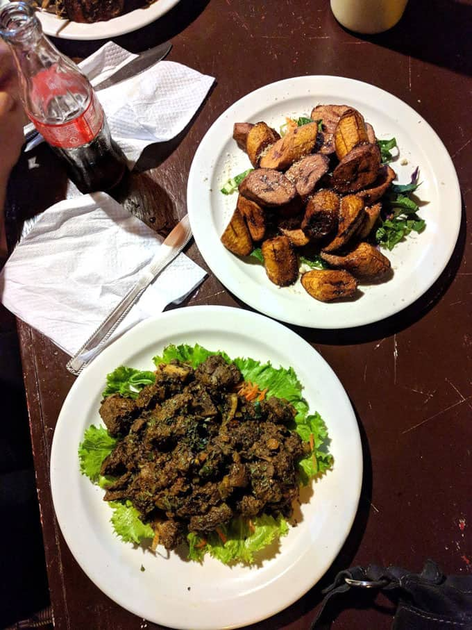 A plate of geera pork and plate of fried plantains on a table.