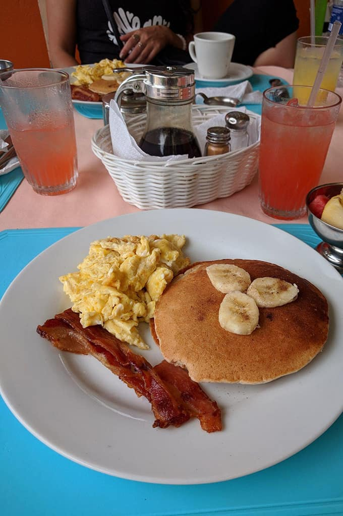 A plate of pancakes, scrambled eggs, and bacon on a table with juice and a basket of syrup, salt, and pepper.