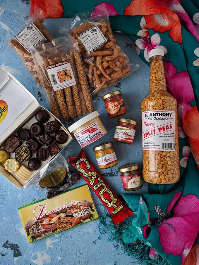 Chocolates, small jars of hot sauce, and packages snacks on a table.