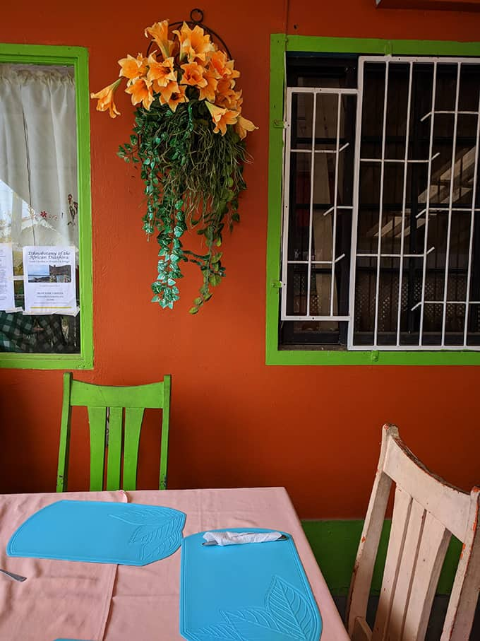 An outdoor dining table in front of a bright orange wall.