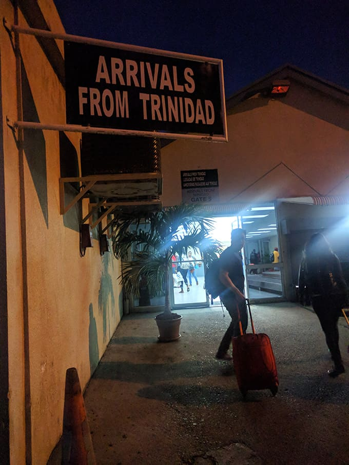 """A sign at the airport that reads \""""arrivals from trinidad.\"""""""