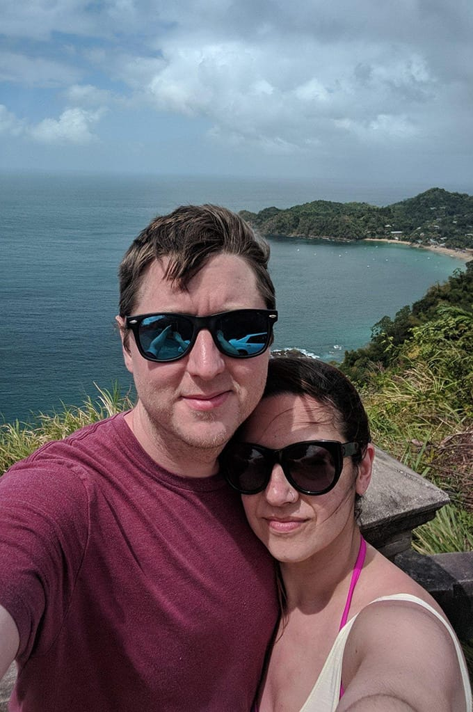 A man and woman wearing sunglasses and standing in front of a cliff overlooking a large body of water.