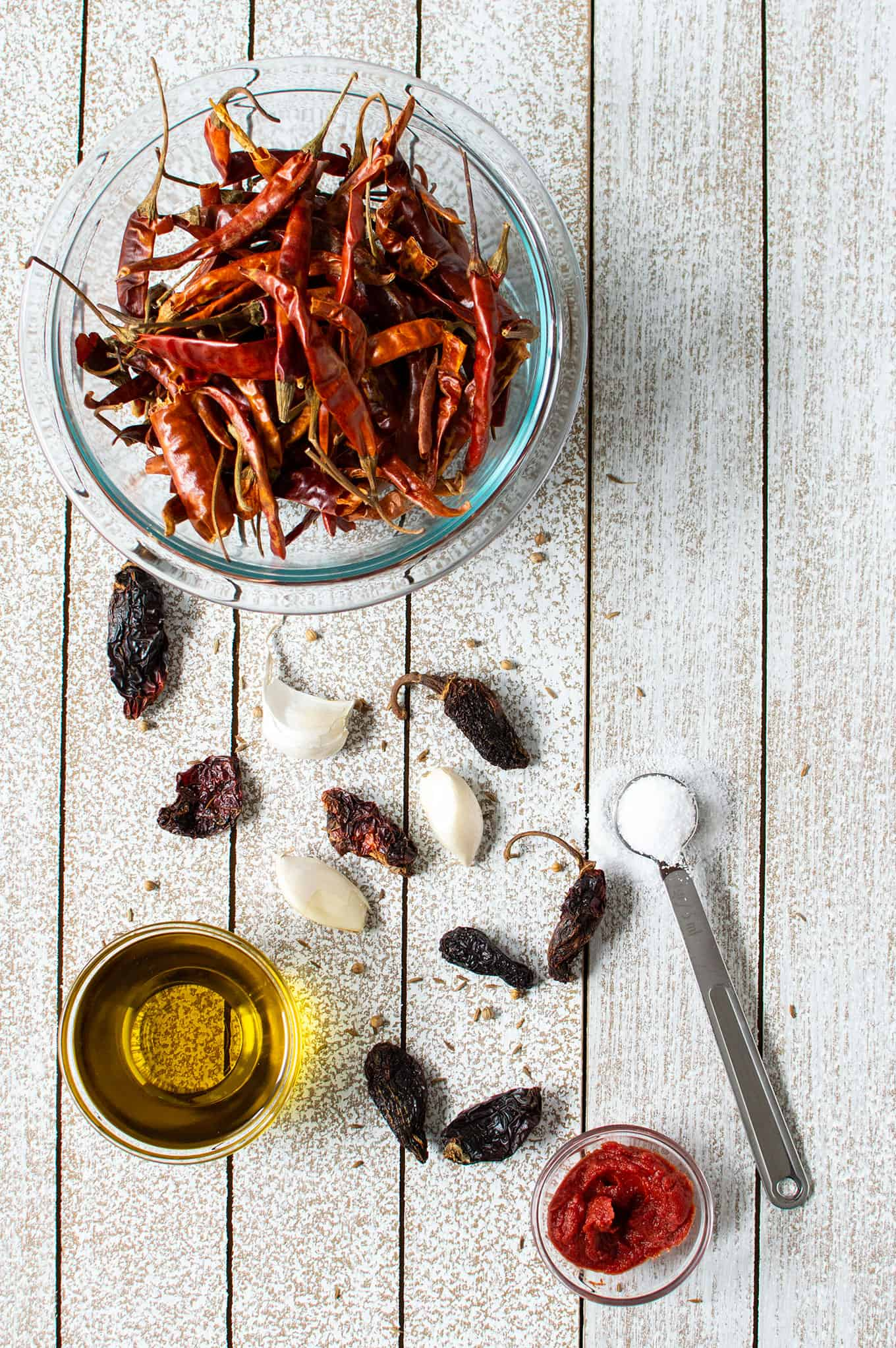 Dried chiles, garlic cloves, salt, and olive oil on a table.