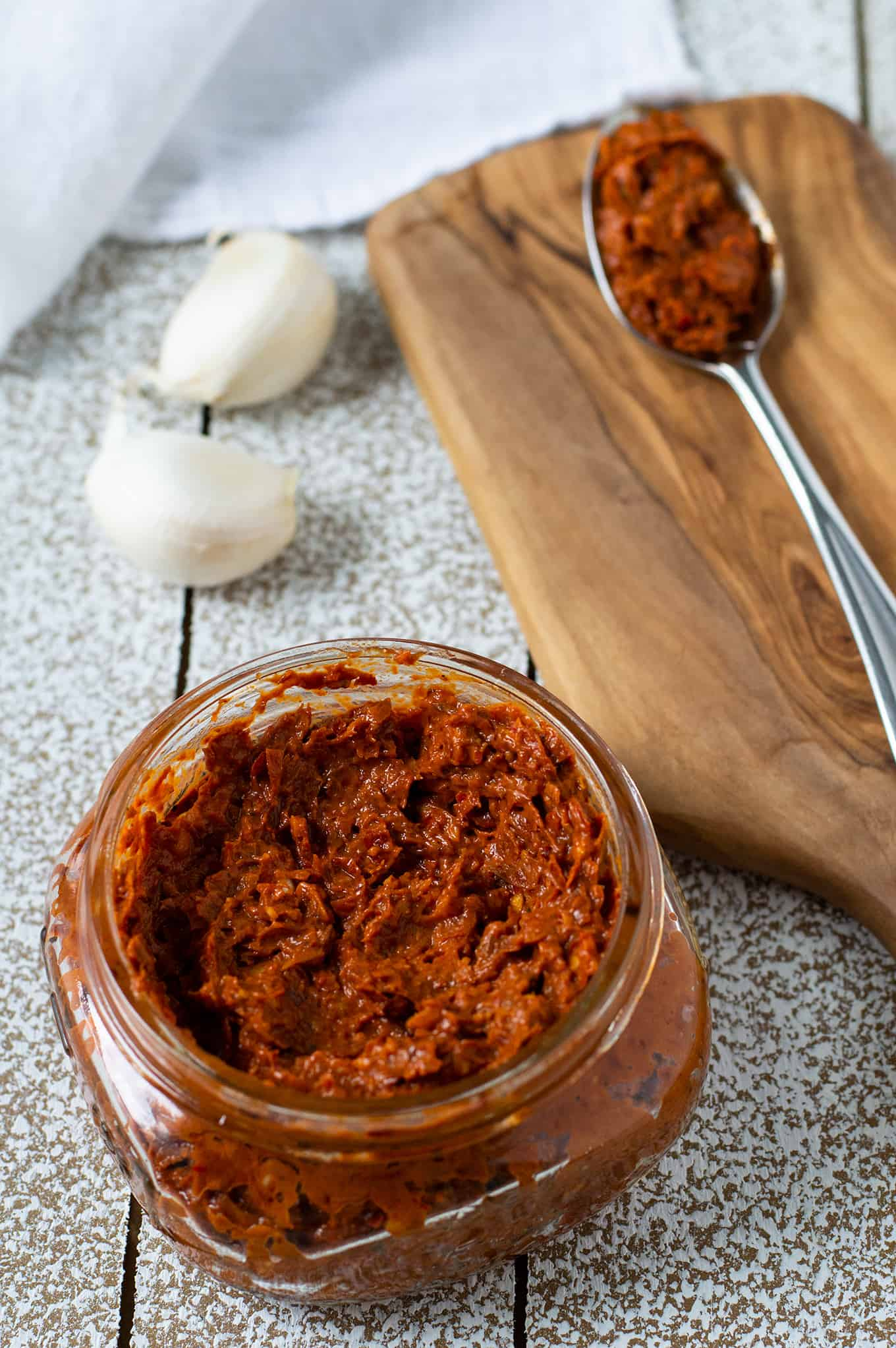 A small jar of harissa paste with a spoon of harissa paste on a table.