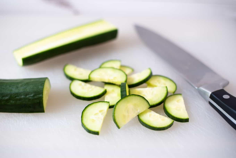 Sliced cucumber on a cutting board.