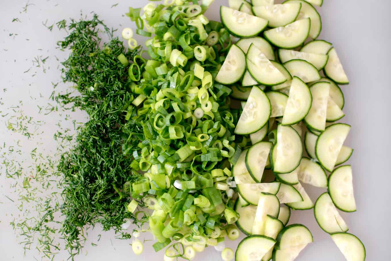 Chopped dill, scallions, and cucumbers on a cutting board.