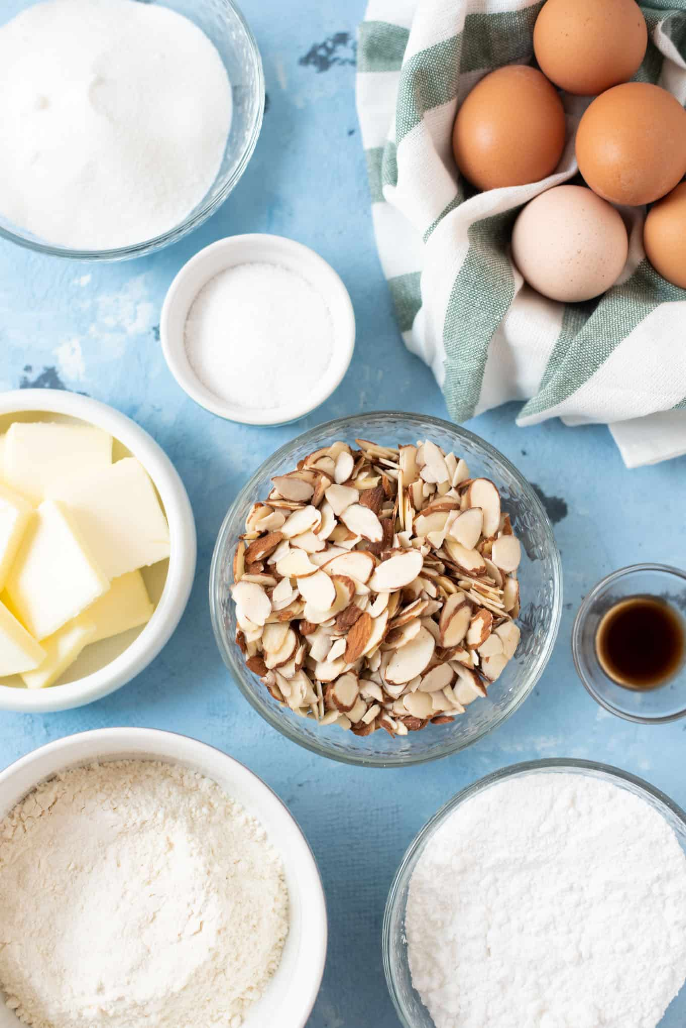 Bowls of butter, sliced almonds, sugar, flour, eggs, and vanilla extract.