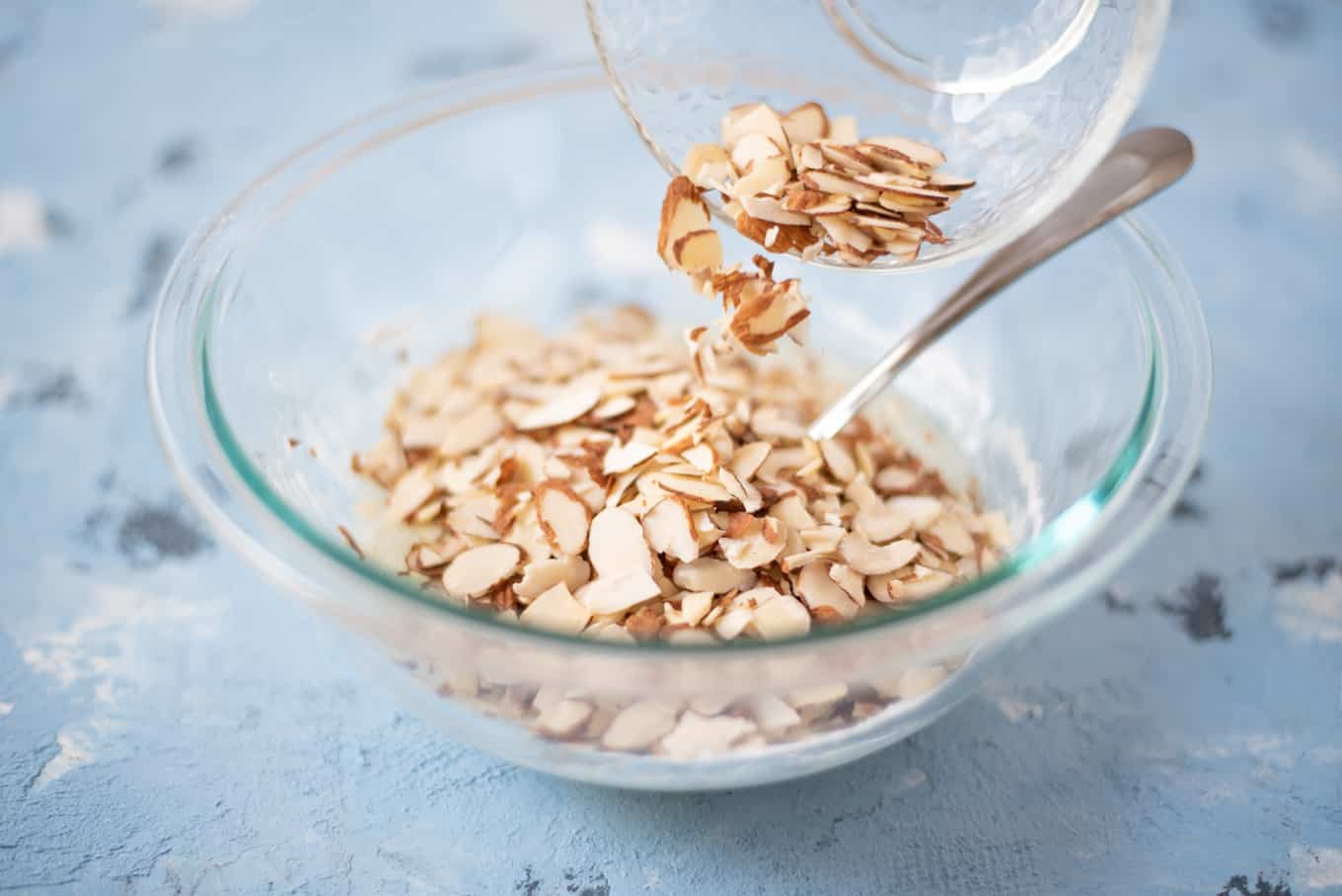 Sliced almonds being poured into a bowl.