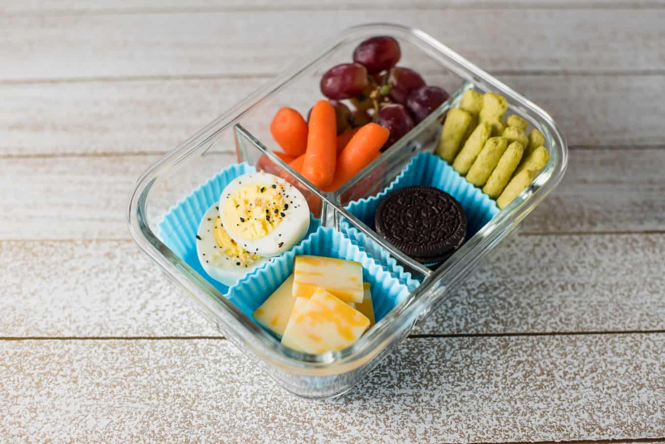 A glass bento box container of cookies, cheese, deviled eggs, fruit, and snacks.