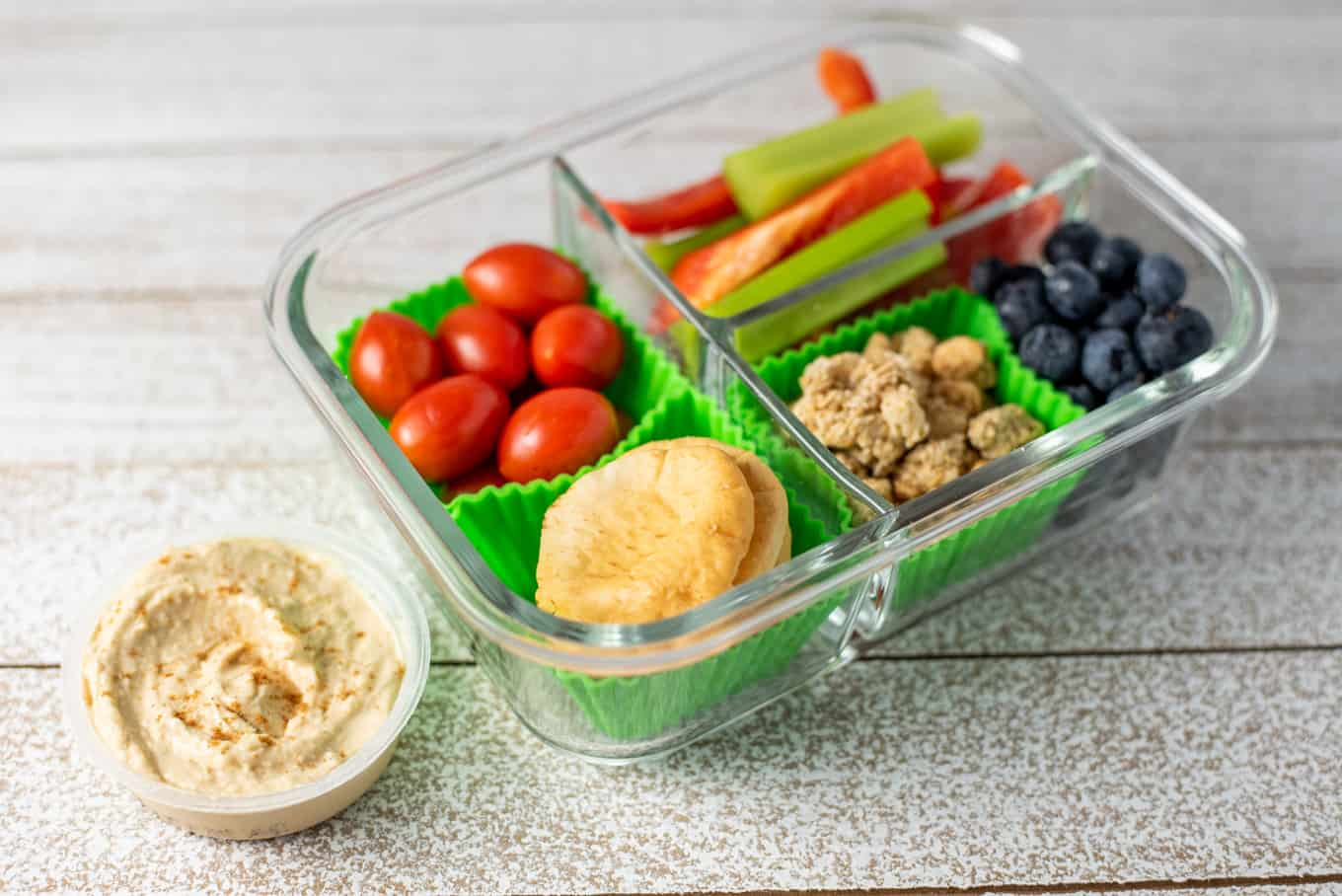 A glass bento box container of crackers, veggie sticks, blueberries, granola, and hummus.