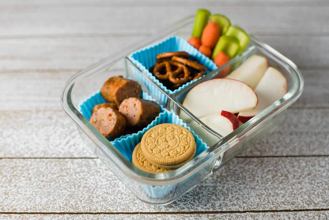 A glass bento box container of cookies, sausage bites, pretzels, apple slices, and veggie sticks.