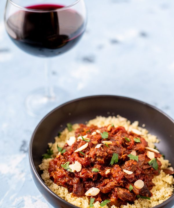 A featured image of lamb tagine in a bowl with a glass of red wine.