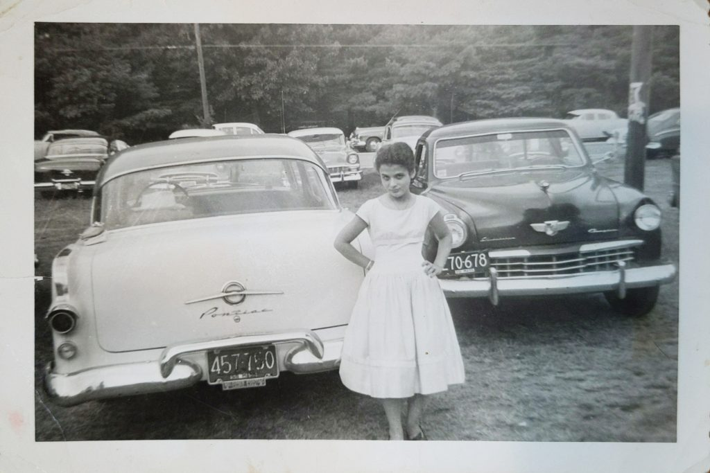 A black and white photo from the 1950s of a woman standing in front of a car.