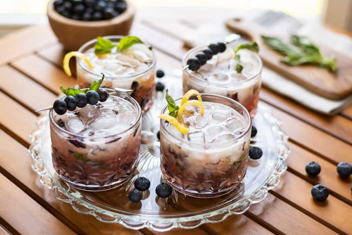 A serving tray with four glasses of blueberry basil bourbon smash. Garnished with fresh blueberries and lemon twist.