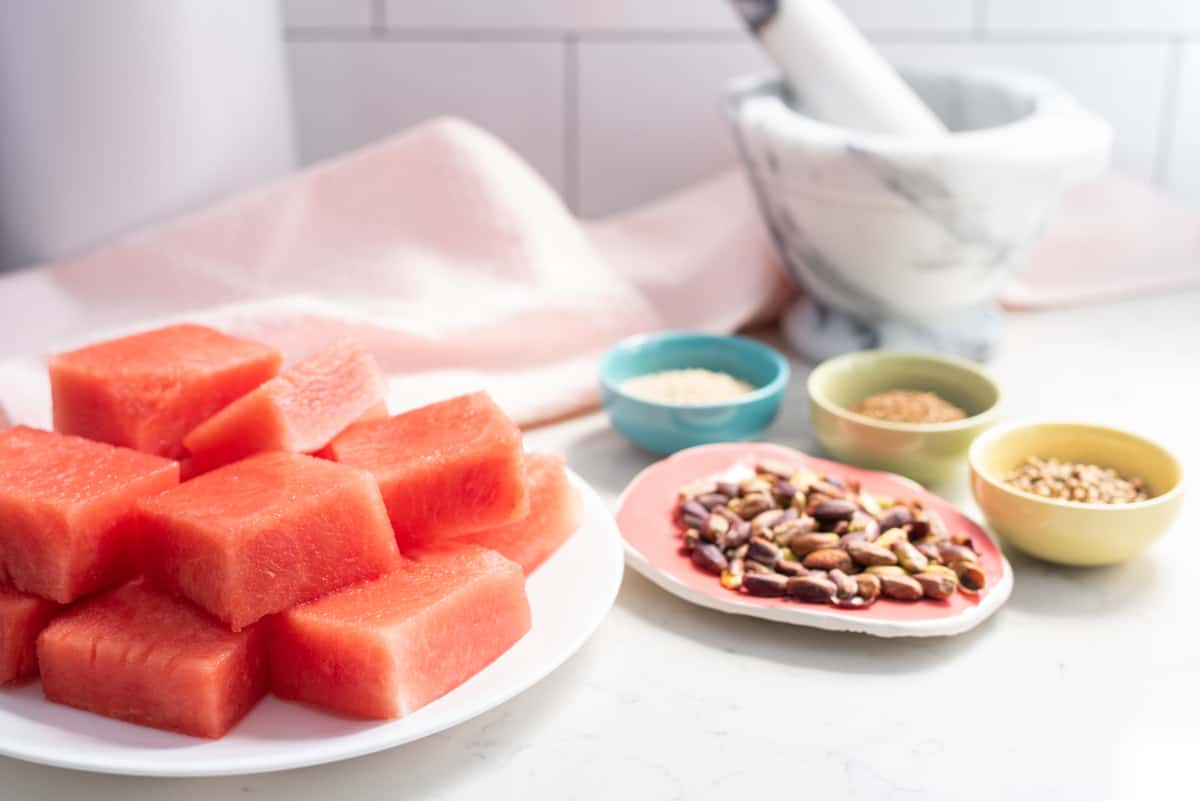 Slices of watermelon on a plate with pistachios, spices, and a mortar & pestle in the background.