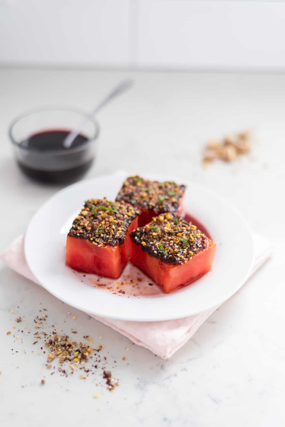 Watermelon topped with harissa, dukkah, and mint with pomegranate molasses in the background.