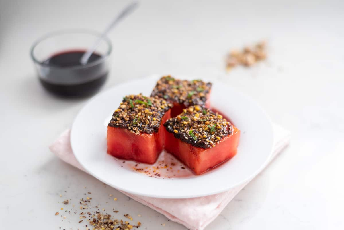 A close-up shot of watermelon topped with harissa, dukkah, and mint with pomegranate molasses in the background.