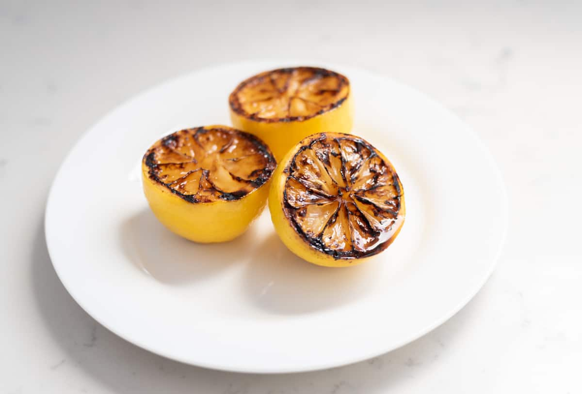 Grilled lemons on a white plate.