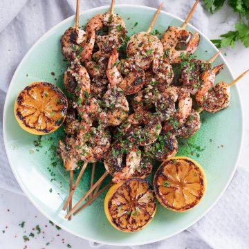 Grilled Turkish shrimp kebabs and grilled lemons on a blue-green plate.