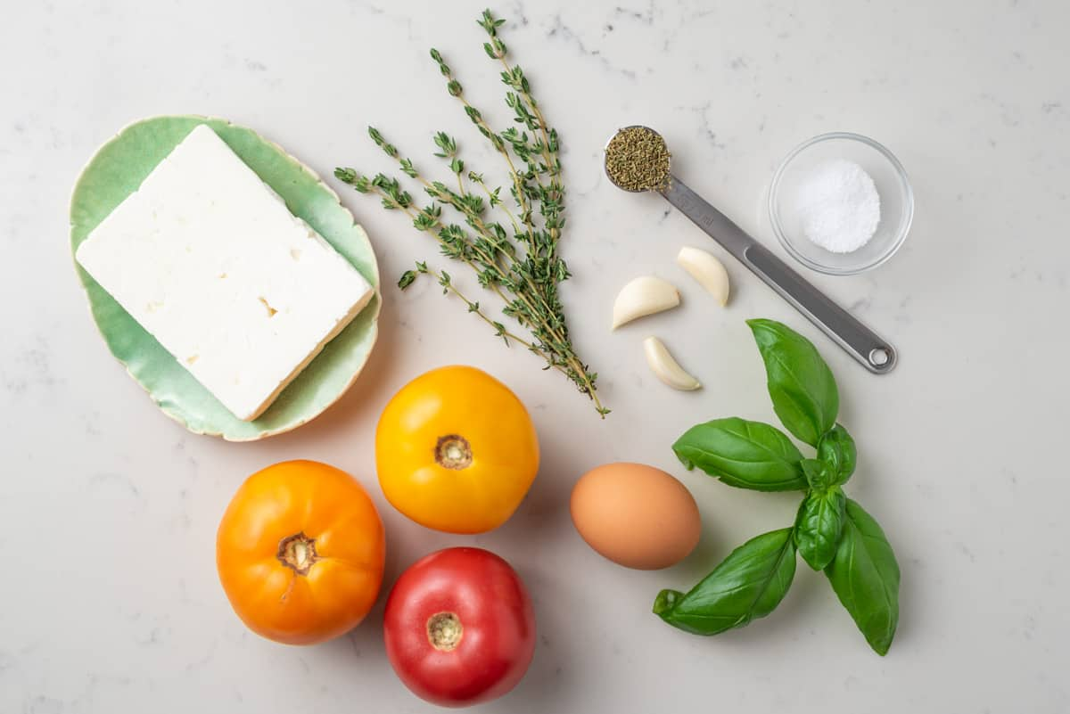 A block of feta cheese, fresh thyme, garlic cloves, tomatoes, an egg, fresh basil leaves, salt, and oregano laid out on a counter top.