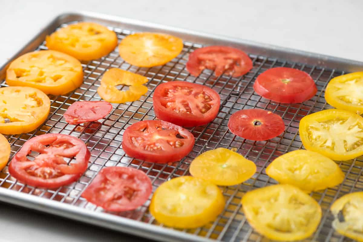 Sliced heirloom tomatoes on a rack-lined baking sheet.