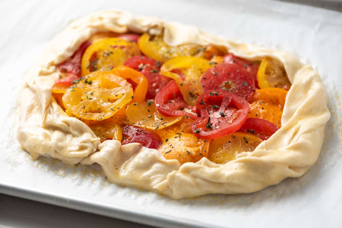 Prepared galette with puff pastry dough; topped with sliced tomatoes and ready for the oven.