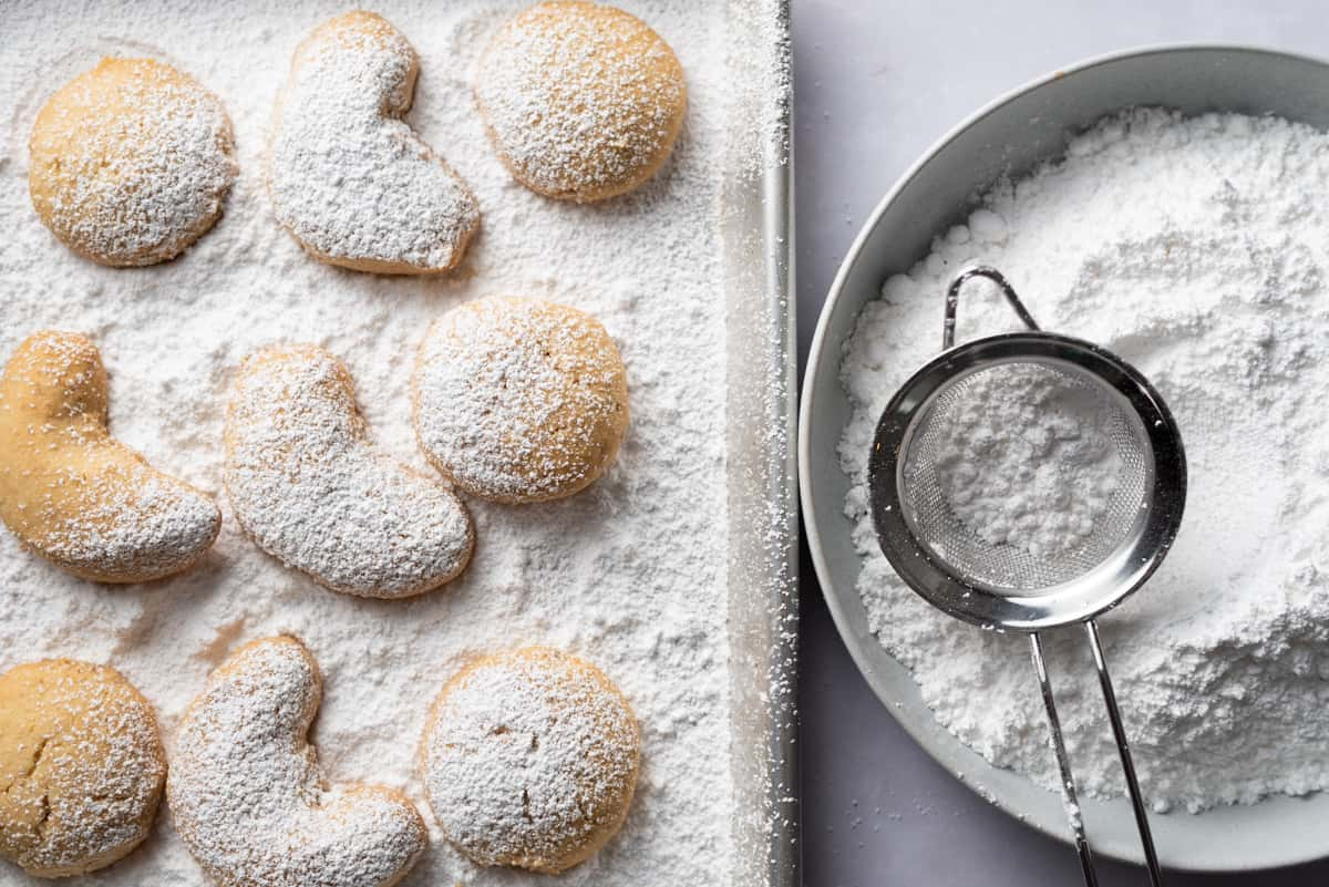 A baking sheet of shortbread cookies partially covered in powdered sugar and a bowl of powdered sugar with a sieve on top.