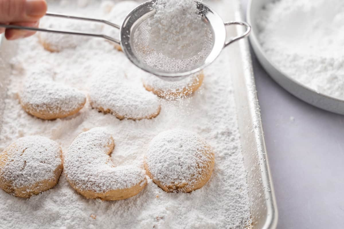 A hand holding a sieve of powdered sugar over shortbread cookies in a baking sheet.