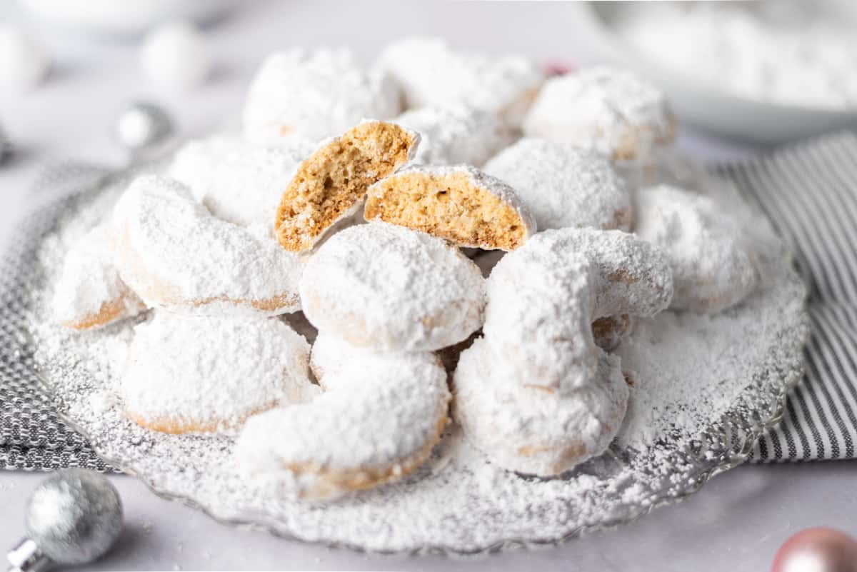 A platter of powdered sugar-covered cookies with a cookie split in half on top.