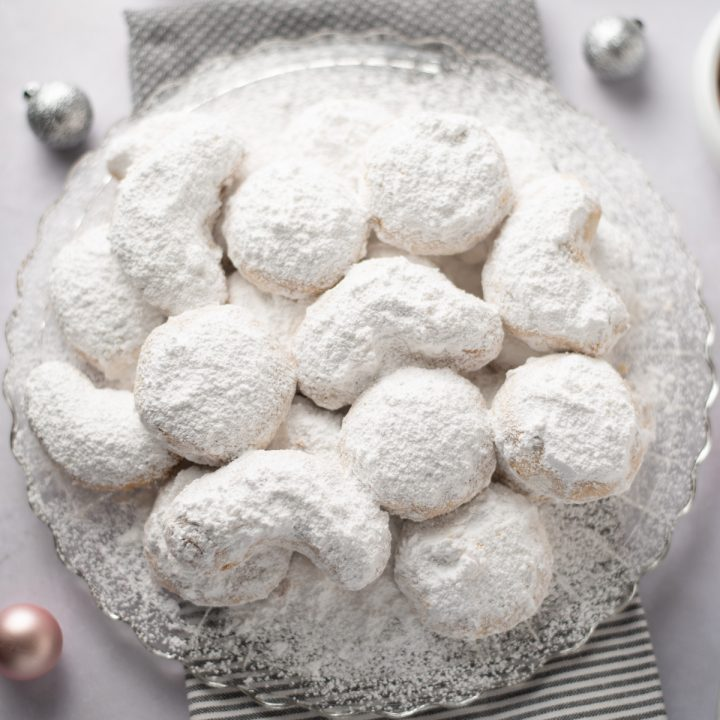 Featured image: Close up of powdered sugar cookies on a platter.