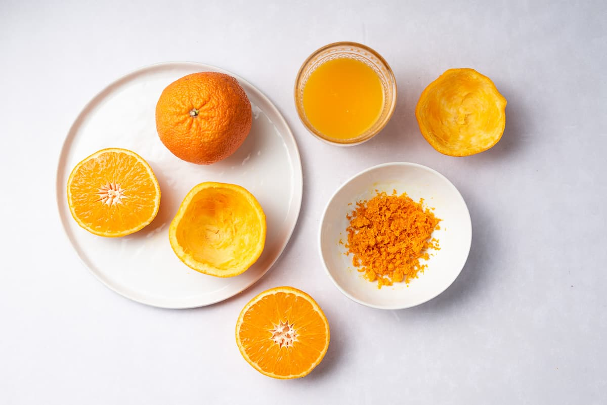 Whole oranges, cut oranges, a bowl of orange zest, and cup of orange juice on a tabletop.