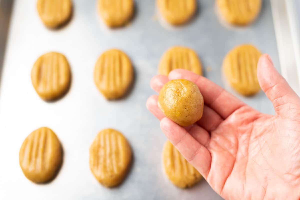 Close up of a hand holding a ball of cookie dough with a baking sheet of prepared cookie dough in the background.