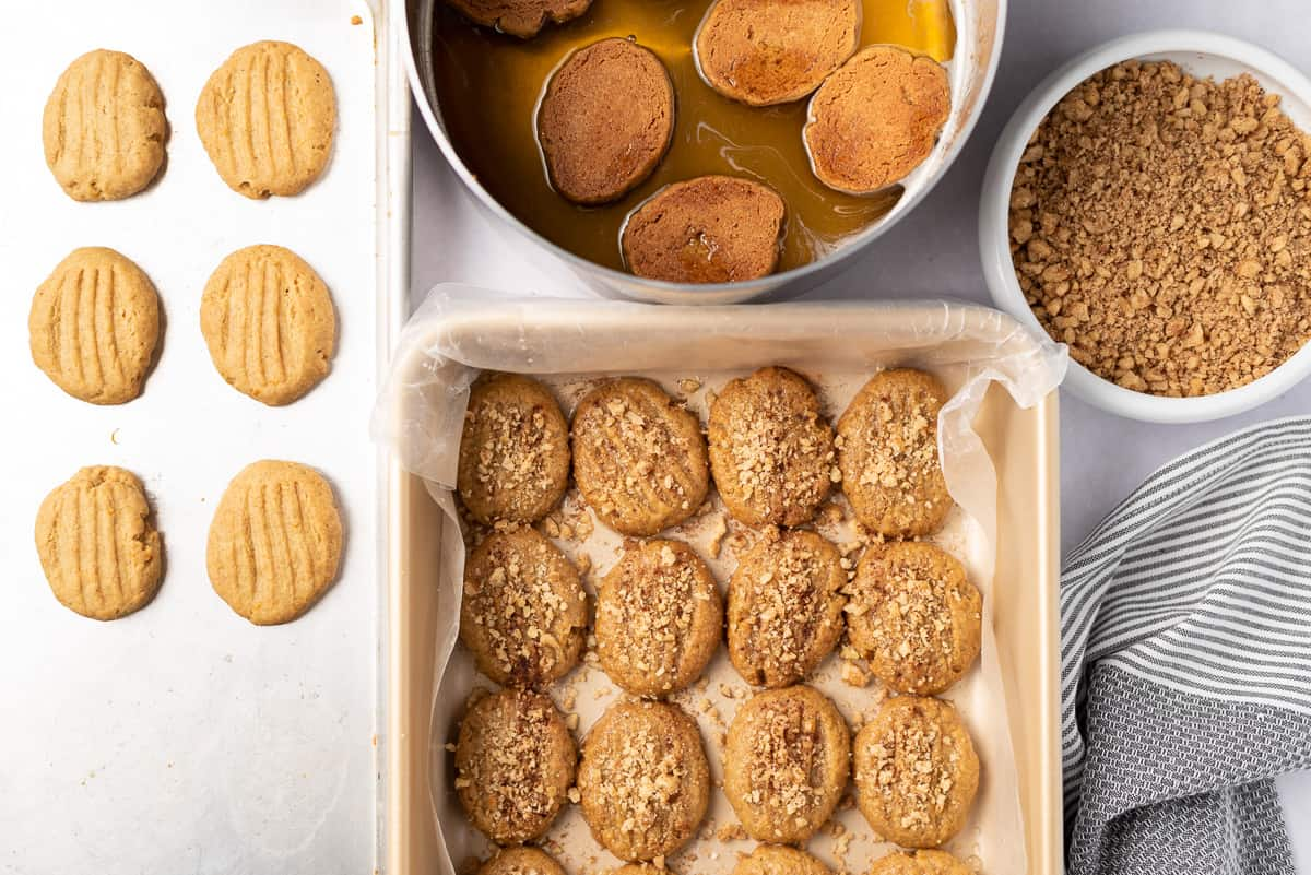 A baking sheet of plain cookies, saucepan of cookies in honey syrup, bowl of chopped walnuts, and wax-lined baking pan of honey-dipped cookies on a tabletop.
