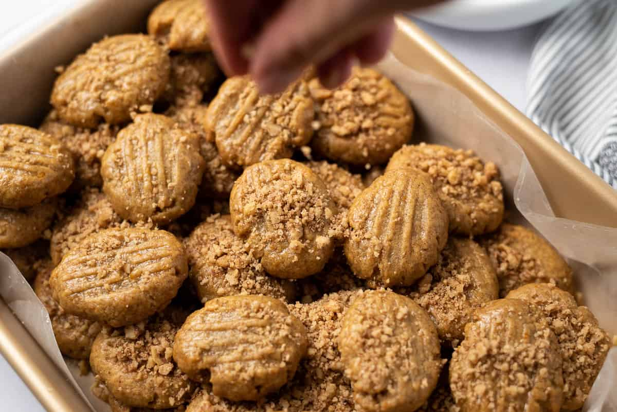 A hand sprinkling chopped walnuts onto Greek honey cookies in a wax-lined baking pan.