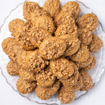 Featured image: Close up of Greek honey cookies stacked on a glass platter.