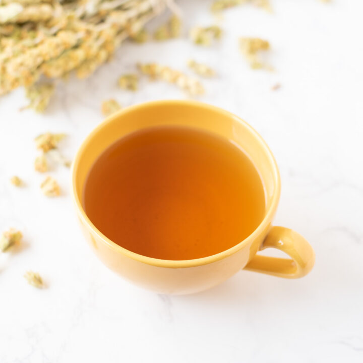 A cup of tea on a table scattered with tea leaves.