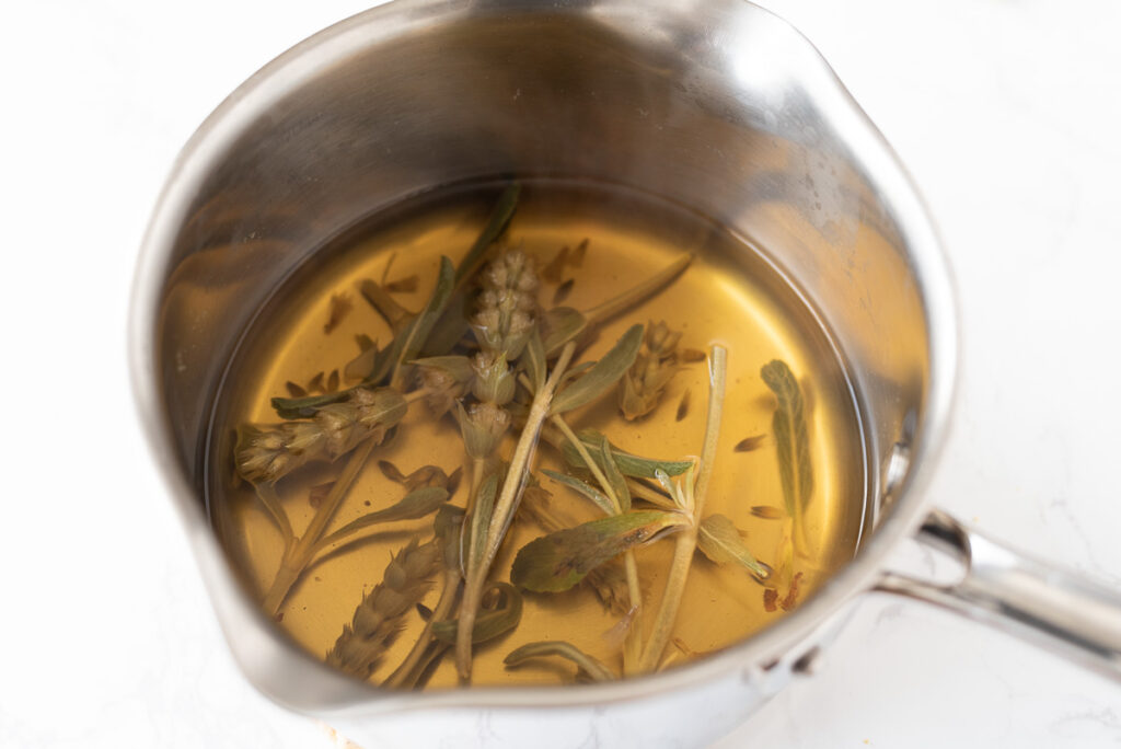 A pot of steeped tea with stems and leaves.