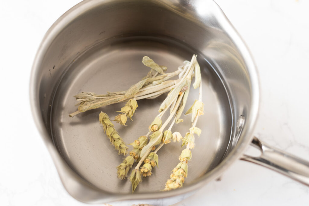 Whole tea stems and leaves steeping in a small pot of water.