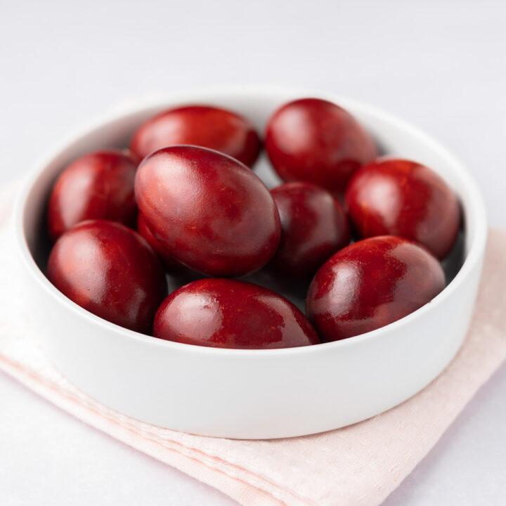 Featured image: a closeup of red-dyed eggs in a white bowl.