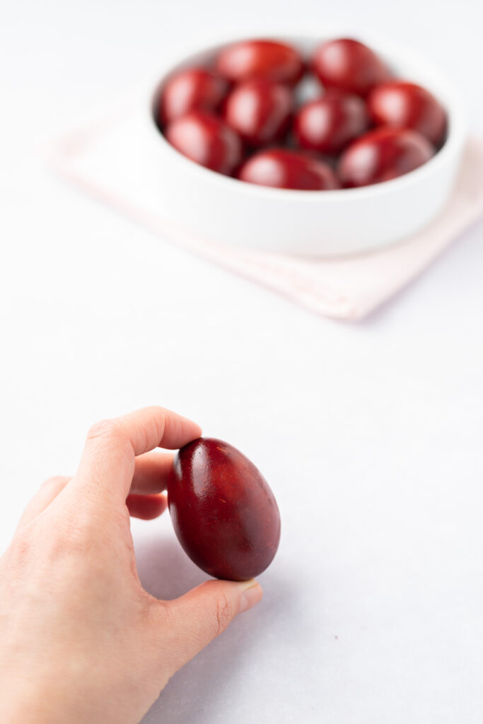 A hand holding a red-dyed egg with a bowl of red eggs in the background.