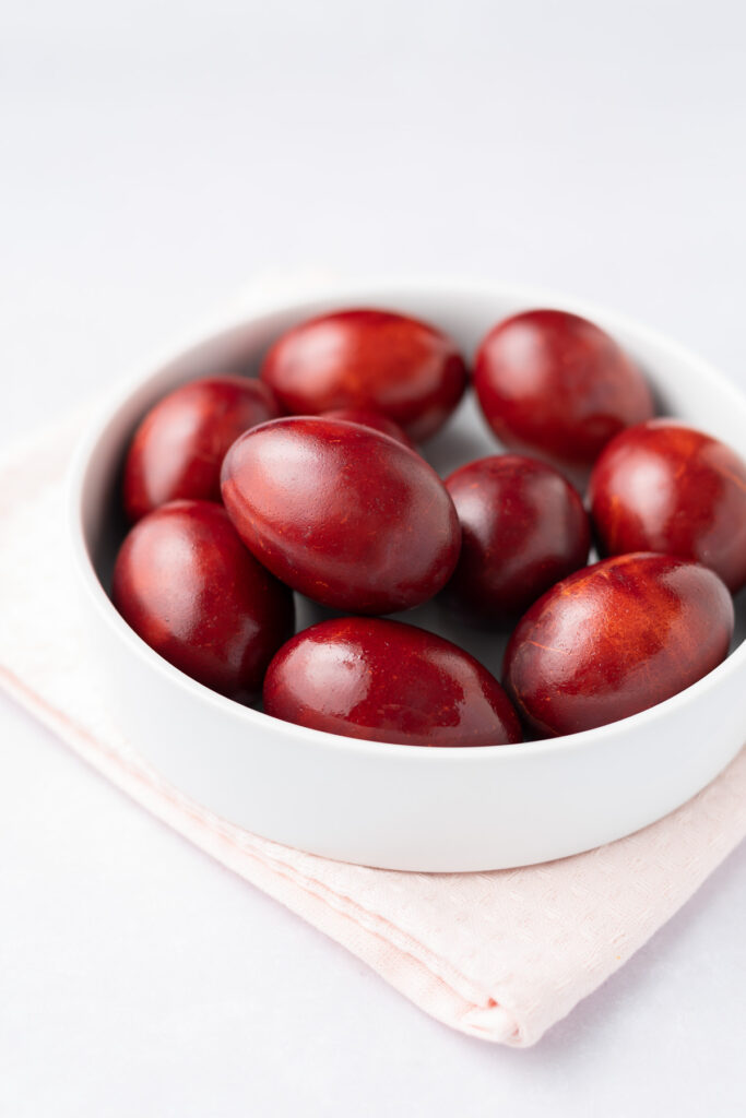 Red-dyed eggs in a white bowl.