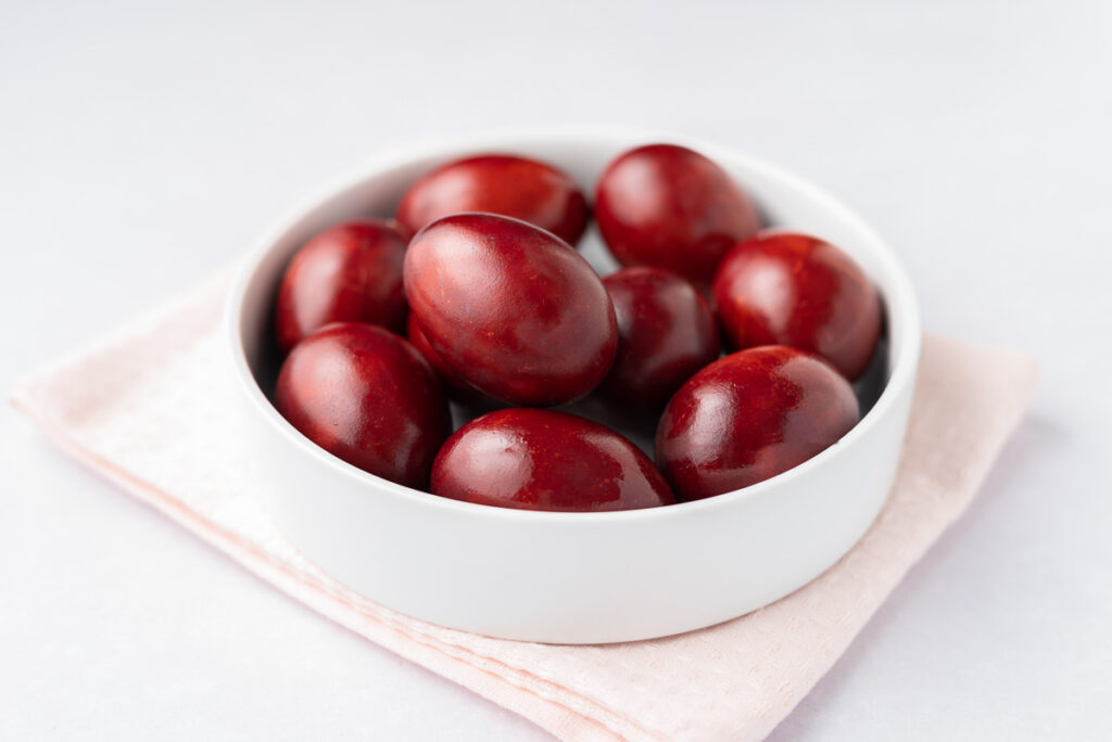 Closeup of red-dyed eggs in a white bowl.