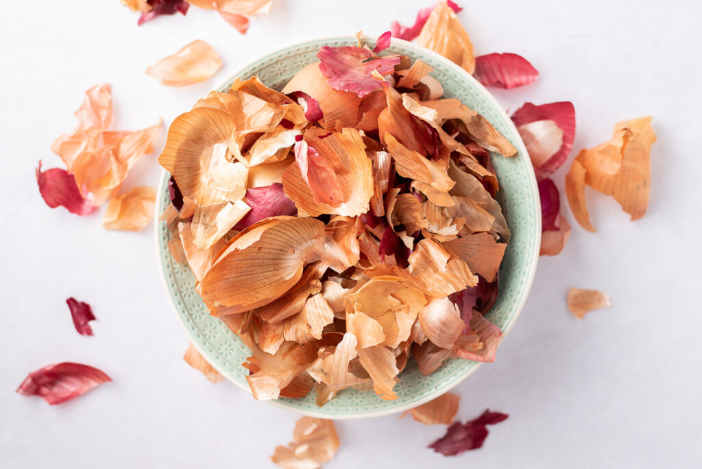 Yellow and red onion skins in a large bowl.